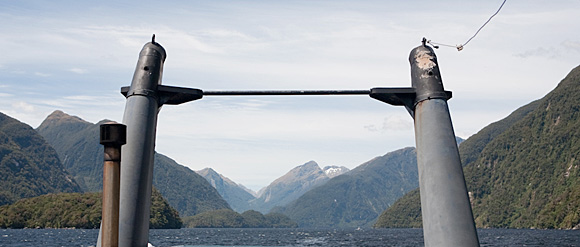 The smokestacks of the M.V. Tutoko, motoring towards the sea on Doubtful Sound, Fiordland National Park, South Island, New Zealand.